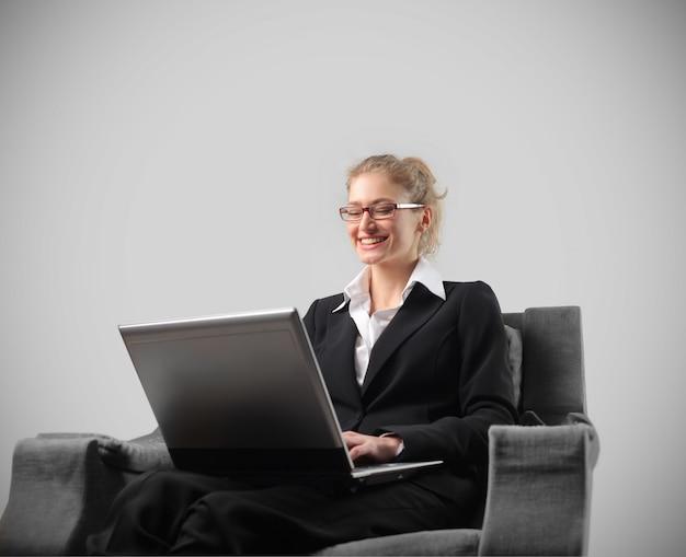 Lachende geschäftsfrau, die an einem laptop arbeitet