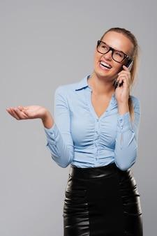 Lachende geschäftsfrau, die auf handy spricht