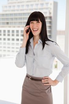 Lachende geschäftsfrau, die einen anruf entgegennimmt