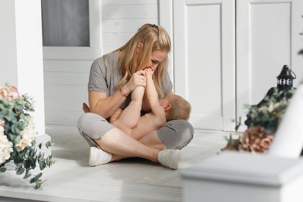 Lachende gesichter der glücklichen familie, mutter, die entzückendes kinderbaby hält