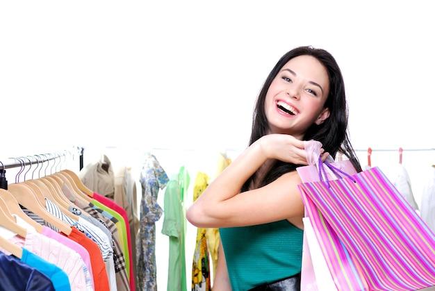 Lachende glückliche frau aus dem einkaufen mit farbigen taschen