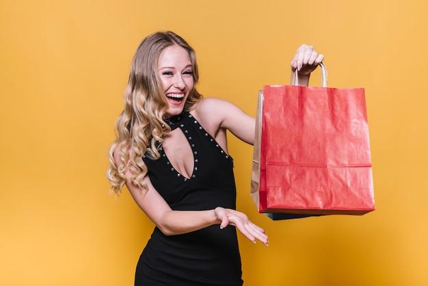 Lachende glückliche frau, die einkaufstaschen zeigt