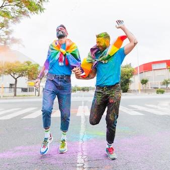 Lachende homosexuelle paare, die auf straße mit regenbogenflagge laufen