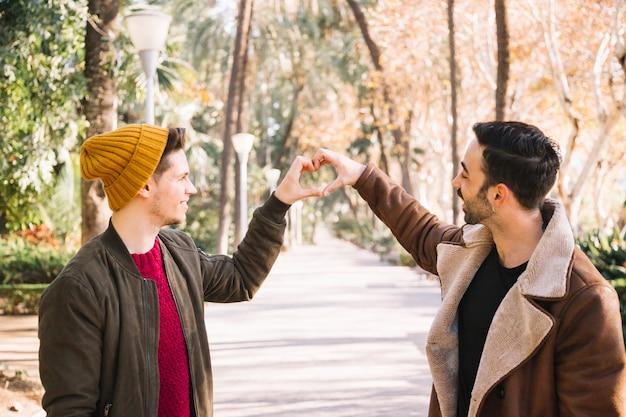 Lachende homosexuelle paare, die herz mit der hand zeigen
