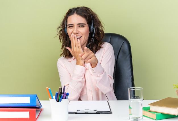 Lachende hübsche kaukasische callcenter-betreiberin auf kopfhörern, die am schreibtisch sitzen, mit bürowerkzeugen, die sich die hand auf den mund legen und nach vorne zeigen