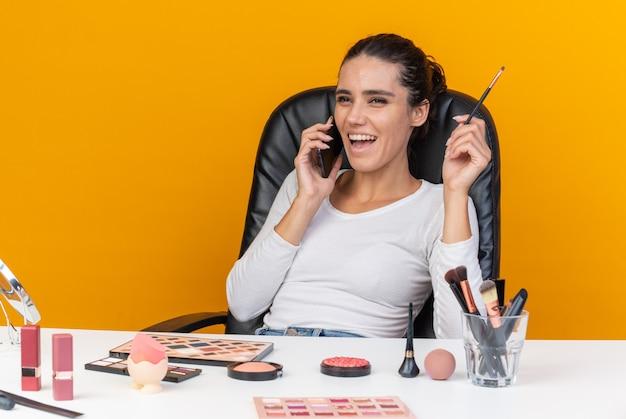 Lachende hübsche kaukasische frau, die am tisch mit make-up-tools sitzt und am telefon spricht und make-up-pinsel hält