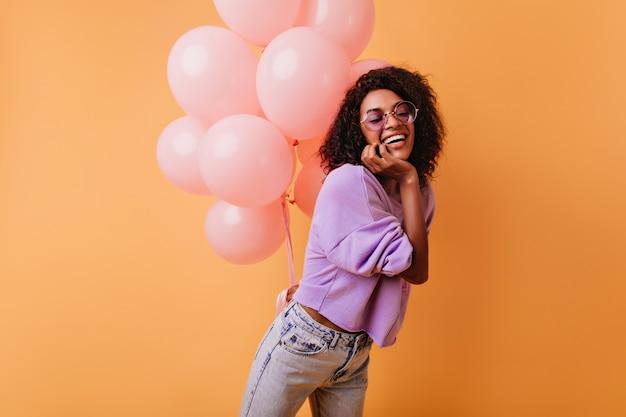 Lachende hübsche schwarze frau, die mit partyballons aufwirft. inspiriertes geburtstagskind mit lockigem haar, das auf orange steht.