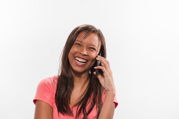 Lachende jugendliche bei der unterhaltung auf mobiltelefon