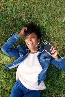 Lachende junge afrikanische frau, die auf gras mit kopfhörern und handy liegt