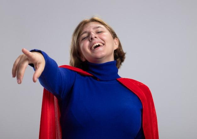 Lachende junge blonde superheldenfrau im roten umhang, der nach vorne lokalisiert auf weiße wand schaut und zeigt