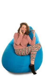 Lachende junge frau, die auf blauem sitzsackstuhl für wohnzimmer oder anderes zimmer sitzt und am telefon lokalisiert auf weiß spricht