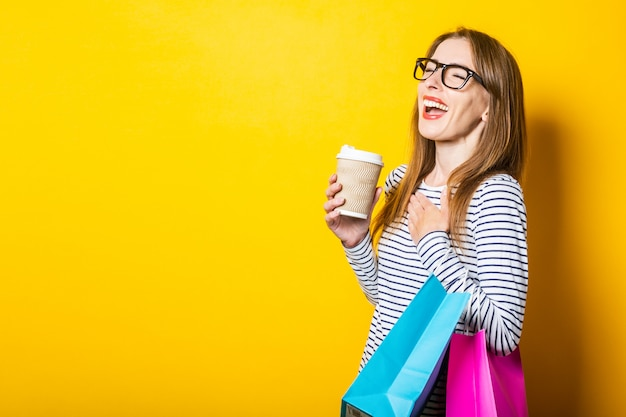 Lachende junge frau freut sich, einen pappbecher mit kaffee und taschen auf gelbem hintergrund zu halten