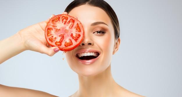 Lachende junge frau hält rote und saftige tomate in den händen mit toothy lächeln und glänzendem gesichtsausdruck