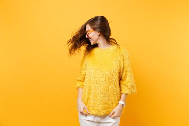 Lachende junge frau im pullover, herzorangefarbene brille, die im studio mit flatternden haaren auf hellgelbem hintergrund herumalbert. menschen aufrichtige emotionen, lifestyle-konzept. werbefläche.