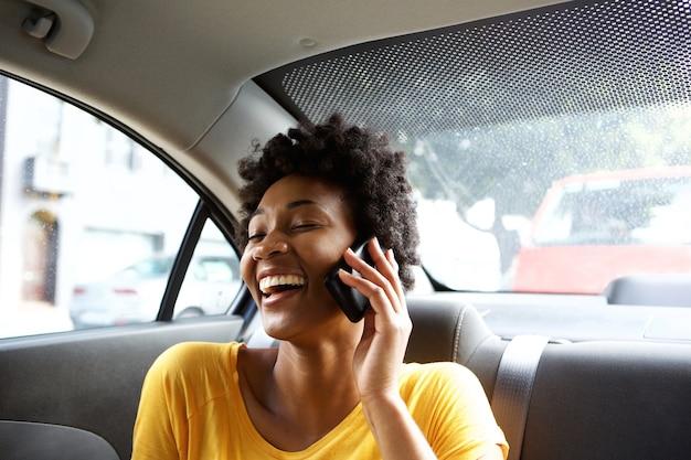 Lachende junge frau in einem auto, das am handy spricht
