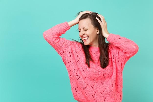 Lachende junge frau in gestricktem rosa pullover mit geschlossenen augen, die die hände auf den kopf legt, einzeln auf blauem wandhintergrund, studioporträt. menschen aufrichtige emotionen, lifestyle-konzept. kopieren sie platz.