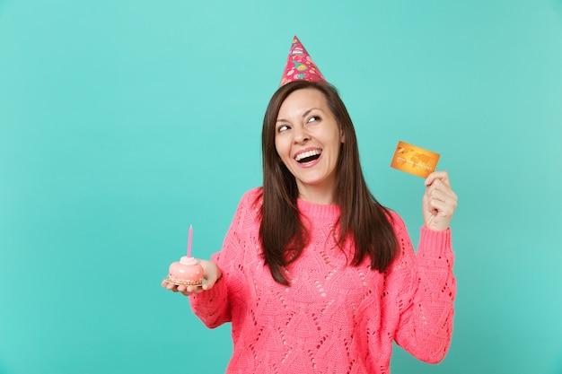 Lachende junge frau in gestrickter rosa pullover-geburtstagsmütze, die in der hand kuchen mit kerze-kreditkarte einzeln auf blauem türkisfarbenem wandhintergrund schaut. menschen lifestyle-konzept. kopieren sie platz.