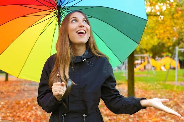 Lachende junge frau mit buntem regenschirm, der für regen prüft