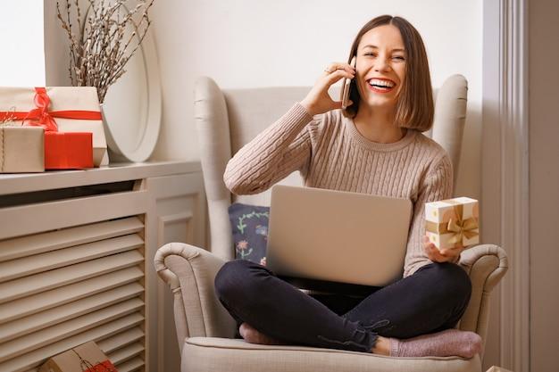 Lachende junge frau mit laptop, die auf handy spricht, während sie in einem bequemen sessel sitzt