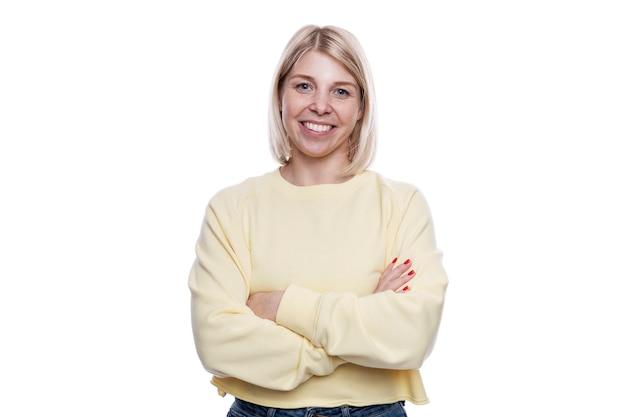 Lachende junge frau mit verschränkten armen auf goudy. blond in einem gelben pullover und jeans.