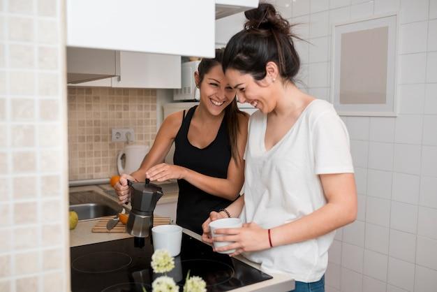 Lachende junge frauen, die in der küche kochen