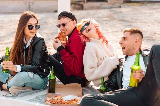 Lachende junge freunde, die spaß auf picknick haben