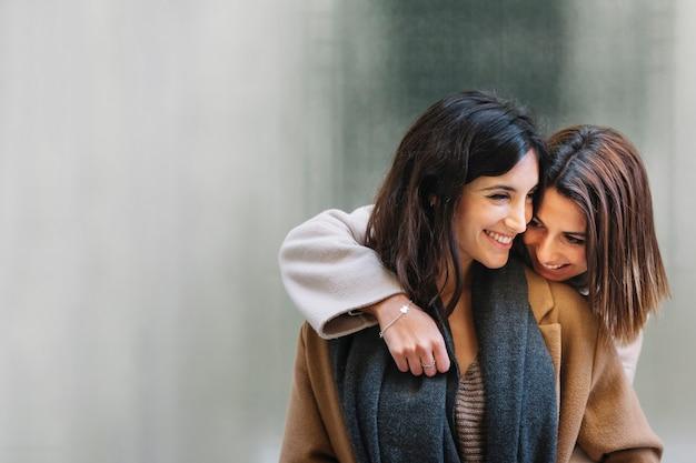 Lachende junge freundinnen, die in der liebe umarmen