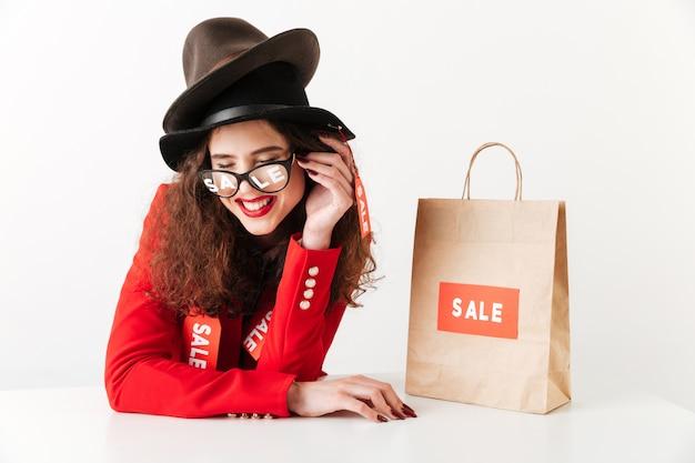 Lachende junge kaukasische dame nahe einkaufstasche