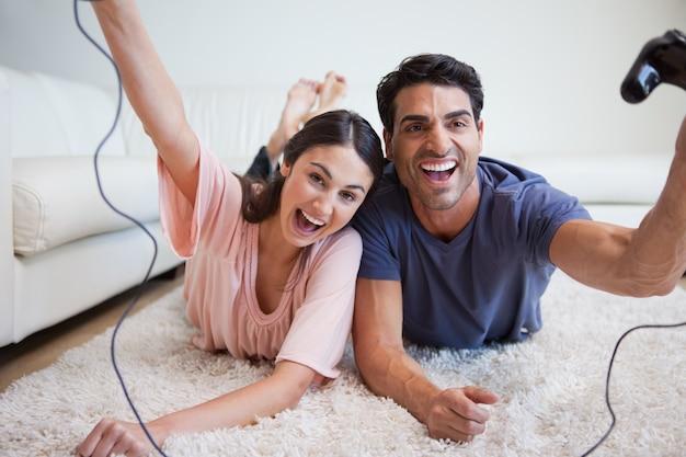 Lachende junge paare, die videospiele spielen