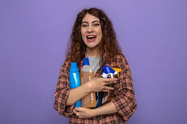Lachende junge putzfrau mit reinigungswerkzeugen