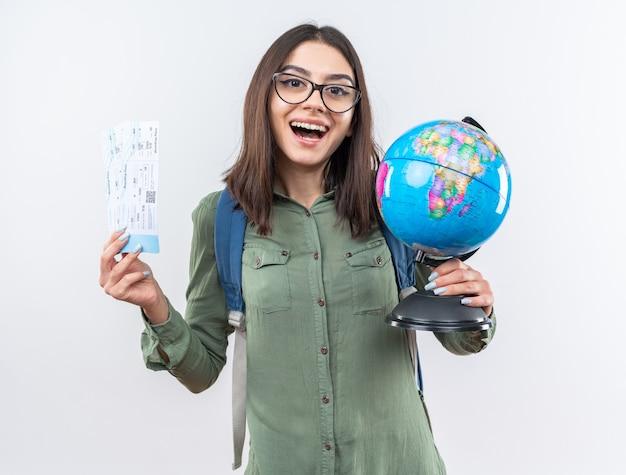 Lachende junge reisende frau mit brille mit rucksack mit tickets mit globus