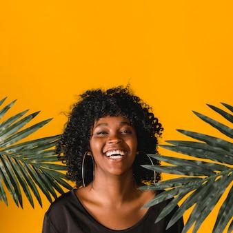 Lachende junge schwarze frau mit palmblättern auf farbigem hintergrund
