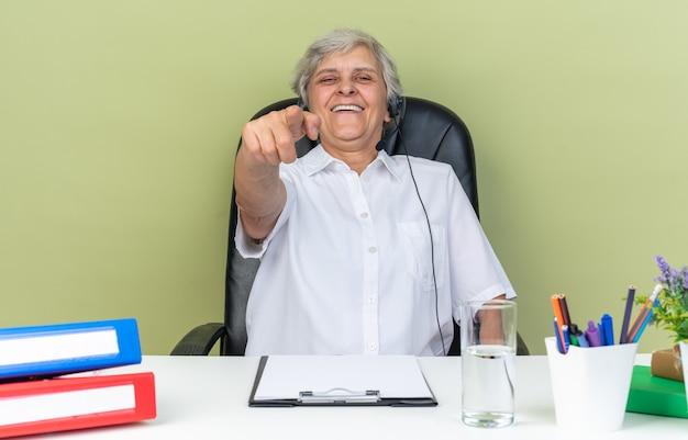 Lachende kaukasische call-center-betreiberin auf kopfhörern, die am schreibtisch sitzen, mit bürowerkzeugen, die isoliert auf grüne wand zeigen