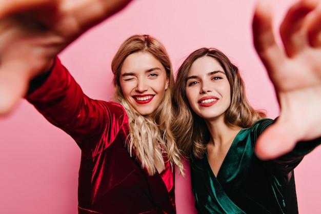 Lachende kaukasische frau mit rotem lippenstift, der selfie auf party macht. ansprechende freundinnen, die zusammen chillen.