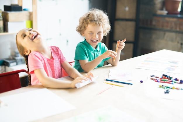 Lachende kinder, die am tisch zeichnen