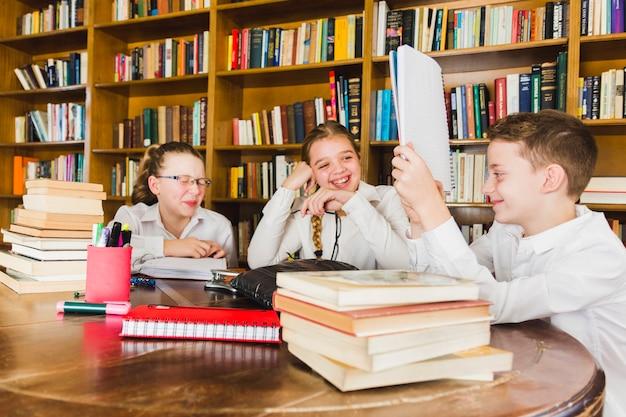 Lachende kinder, die schreibheft in der bibliothek betrachten