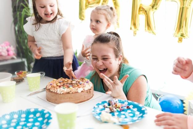 Lachende kinder und teenager, die kuchen schmecken