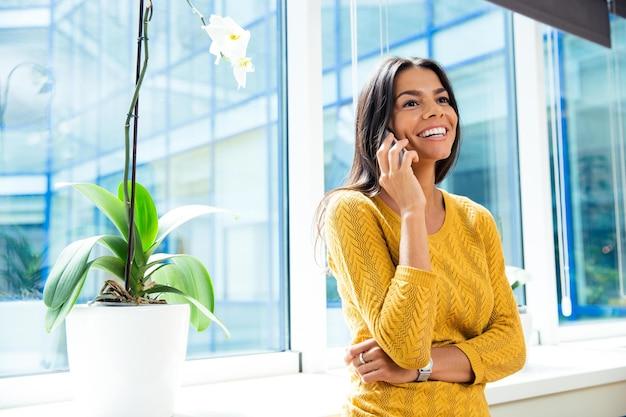 Lachende lässige geschäftsfrau, die im büro in der nähe des fensters auf dem smartphone spricht und wegschaut