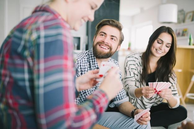 Lachende leute, die spaß mit kartenspiel haben