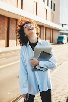 Lachende lockige dame mit brille, die draußen mit einem computer aufwirft