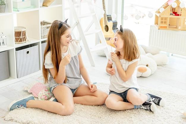 Lachende mädchen, die sich mit brille auf stöcken im kinderzimmer ansehen