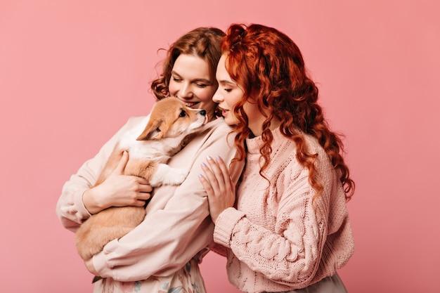 Lachende mädchen, die welpen betrachten. studioaufnahme der entzückenden damen mit dem hund, der auf rosa hintergrund aufwirft.