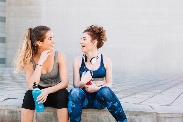 Lachende mädchen in der sportkleidung, die auf straße sitzt