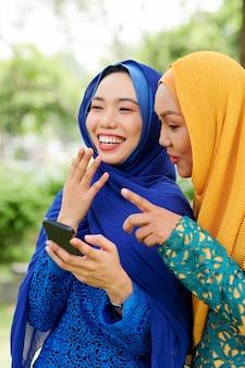 Lachende muslimische frauen mit smartphone