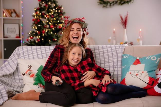Lachende mutter mit stechpalmenkranz hält tv-fernbedienung und schaut in die kamera mit tochter, die auf der couch sitzt und die weihnachtszeit zu hause genießt