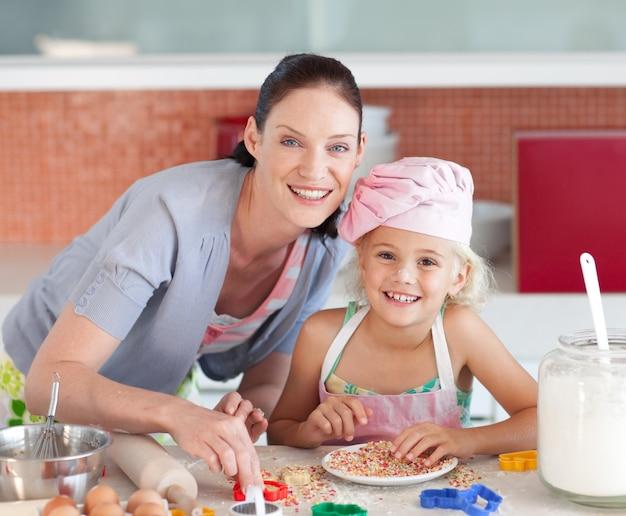 Lachende mutter und ihre tochter in einer küche backen