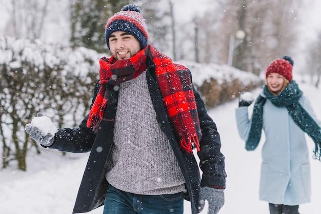 Lachende paare, die schneebälle spielen