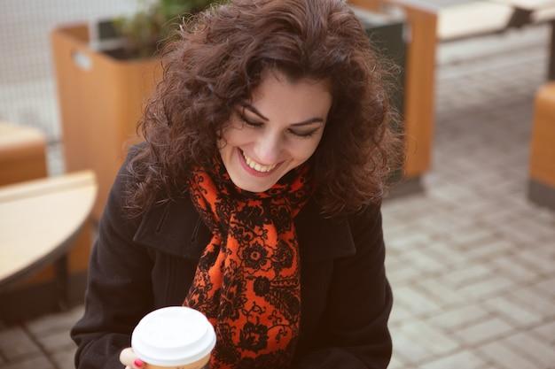 Lachende schönheit auf der terrasse eines straßencafés mit einer tasse heißen kaffees