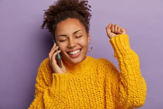 Lachende sorglose lockige ethnische frau spricht auf smartphone