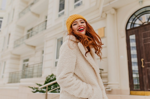 Lachende spektakuläre frau, die im kalten tag aufwirft. außenporträt des attraktiven mädchens mit hellem make-up, das winter genießt.